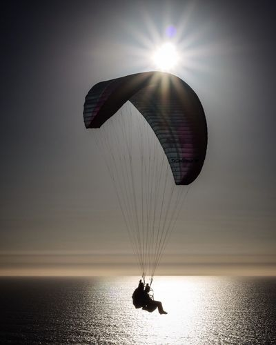 Silhouette people paragliding over sea against bright sky