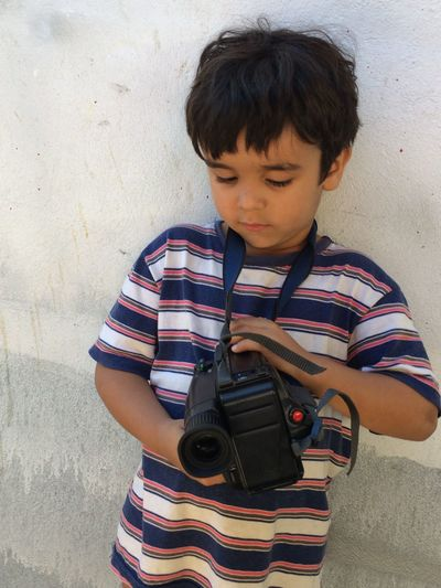 High angle view of boy with camera standing by wall