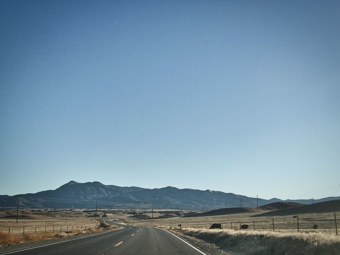 Road by landscape against clear blue sky
