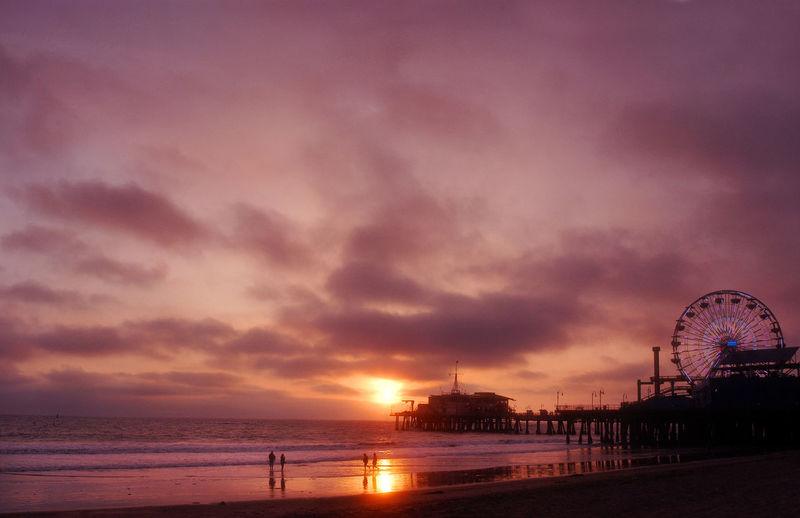 Santa Monica Pier At Beach Against Sky During Sunset
