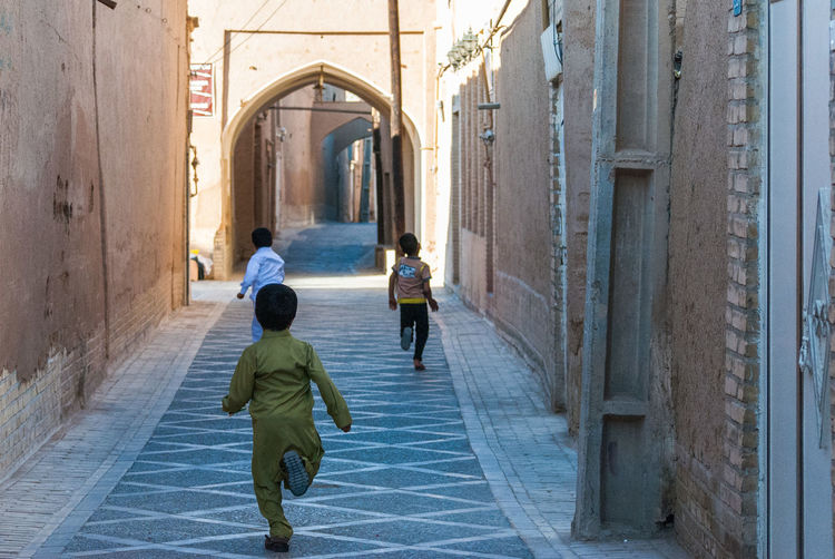 Iranian children running into the future Child Children Persian Cat  Iranian People Iranian Iran Outdoors Lifestyles Real People Day Full Length Building Rear View People Women Men The Way Forward Arch Direction Adult Walking Building Exterior Built Structure Architecture Yazd