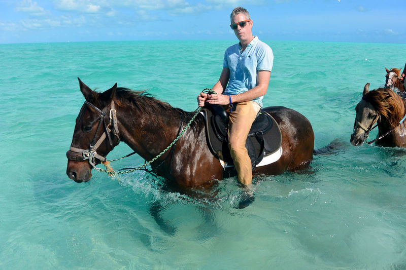 Full length of man riding horse in sea