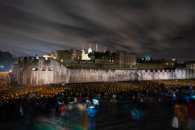 LONDON, UK - NOVEMBER 06, 2018: The Tower of London's moat has been filled with around 10,000 lit torches to mark the centenary of the end of the First World War. Architecture Built Structure Illuminated Crowd Building Exterior Group Of People Sky City Night Large Group Of People Building Dusk Water Men Reflection Travel Destinations Outdoors Light Tower Of London Armistice Remembrance Day ArmisticeDay First World War Torches Moat