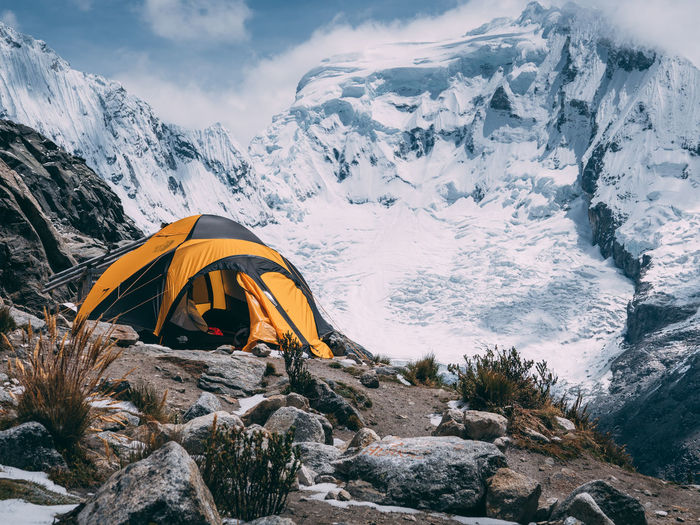 Tent by snowcapped mountains against sky