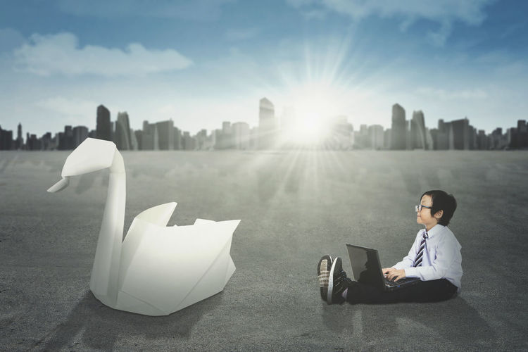 Digital composite image of boy using laptop on road against sky in city during sunny day