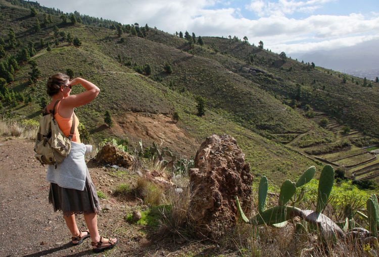 Woman standing on landscape against mountain