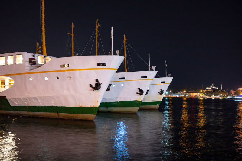 Sailboats moored in marina at night