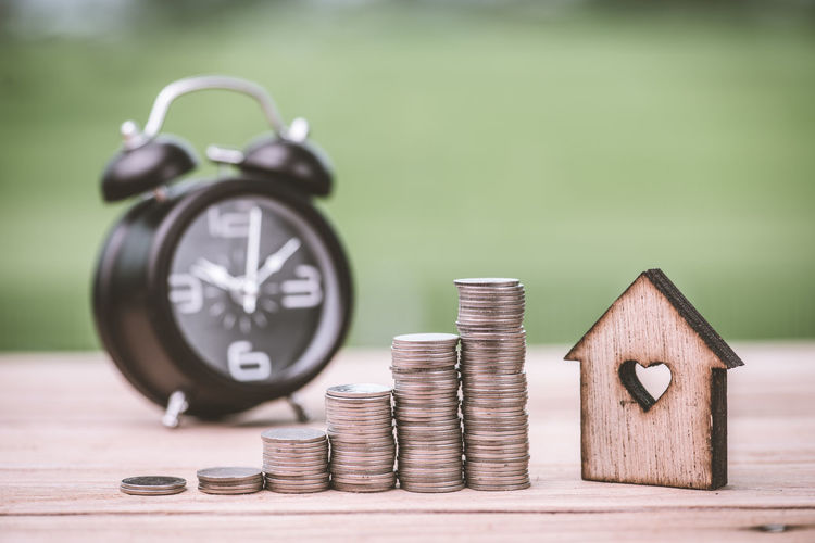 Finance Savings Focus On Foreground Coin Wealth No People Close-up Still Life Business Currency Wood - Material Table Metal Investment Number Shape Selective Focus Economy Finance And Economy Green Color Silver Colored Clock Small