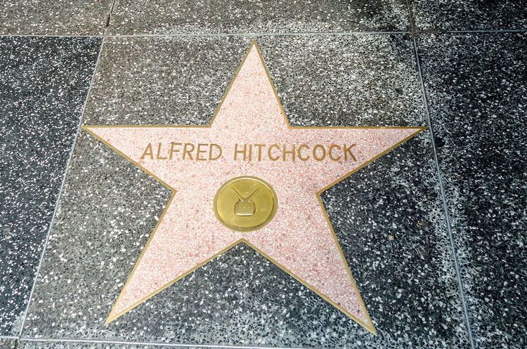 HOLLYWOOD - AUGUST 26, 2012: Alfred Hitchcock's star on Hollywood Walk of Fame, as seen on August 26, 2012 in Hollywood in California. This star is located on Hollywood Blvd. and is one of 2400 celebrity stars. Architecture Arrow Symbol Art And Craft City Communication Day Directional Sign High Angle View Marking No People Outdoors Road Shape Sign Star Shape Street Symbol Text Textured  Transportation