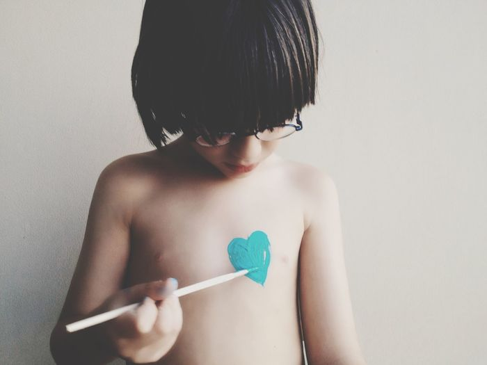Shirtless Boy Painting Heart Shape On Chest At Home