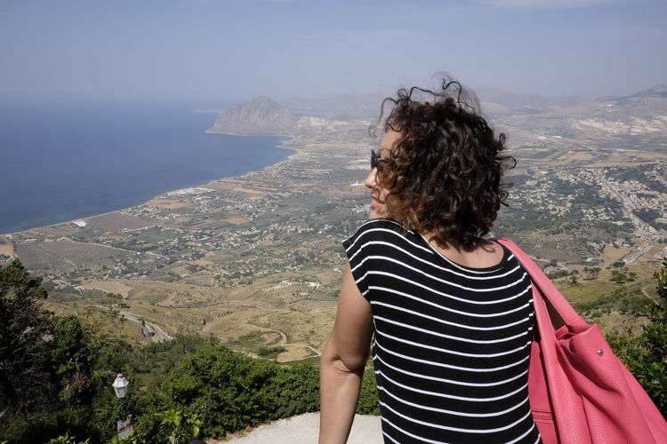 Rear view of woman looking at view from observation point at erice