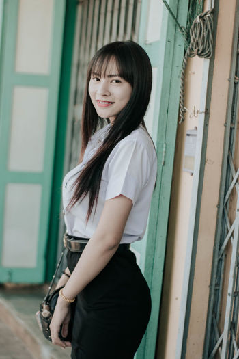 Portrait of smiling young woman standing against door