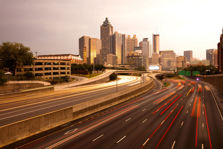 Downtown city skyline at dusk of Atlanta, Georgia, USA City Cityscape Downtown Georgia Light Trails Lights Road Skyline USA Architecture Atlanta Building Exterior Buildings Dusk Expressway Freeway Highway Illuminated Midtown Motion Night Office Building Streaking Lights Susnet Transportation