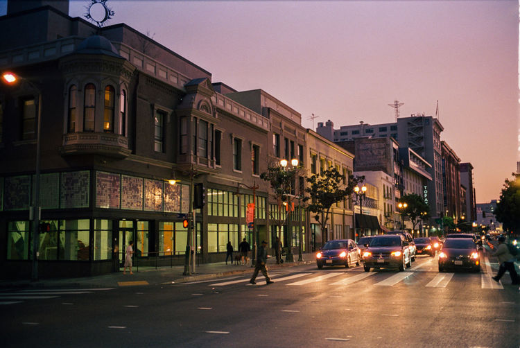 Cars on road by illuminated buildings in city at dusk