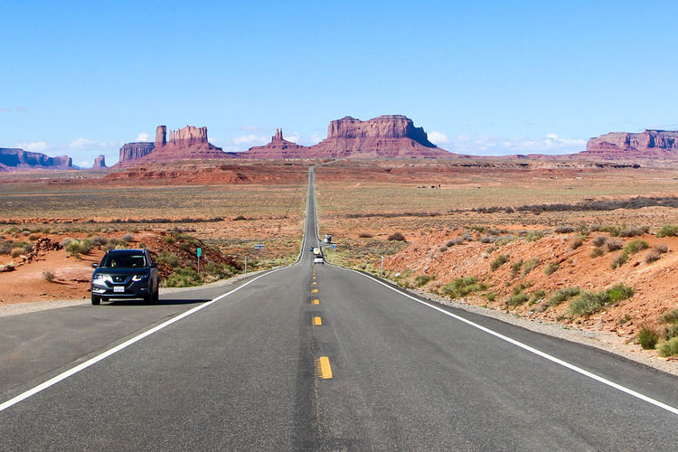 Road Direction The Way Forward Transportation Sign Sky Symbol Marking Road Marking Nature Scenics - Nature Landscape Day Mountain Non-urban Scene Car Motor Vehicle Environment Mode Of Transportation Land Vehicle Diminishing Perspective No People Climate Outdoors Arid Climate Monument Valley Arizona