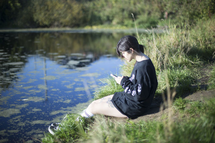 Day Full Length Grass Lake Nature One Person Outdoors People Phoneaddict Sitting Tree Water Young Adult