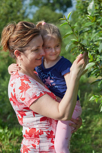 Smiling mother with daughter touching plants at agricultural field
