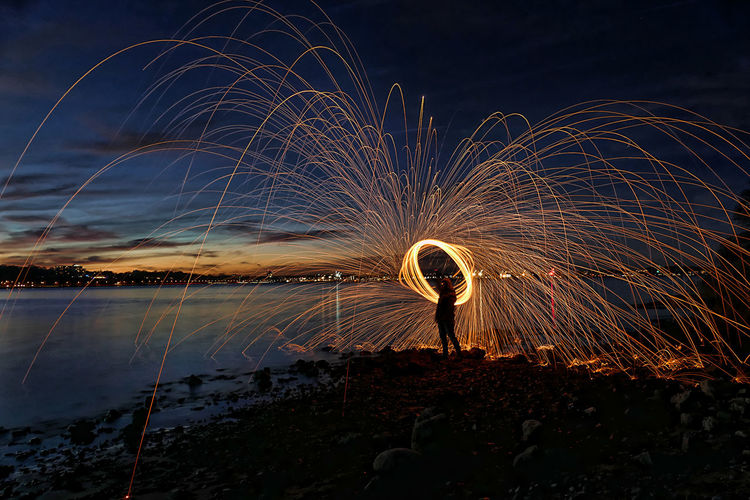 Silhouette person standing by wire wool at beach against sky at night