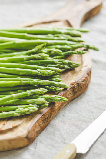 Food Food And Drink Freshness Healthy Eating Wellbeing Vegetable Asparagus Table Indoors  Close-up Still Life Green Color No People Wood - Material High Angle View Selective Focus Focus On Foreground Raw Food Cutting Board Kitchen Knife Herb Table Knife Vegetarian Food
