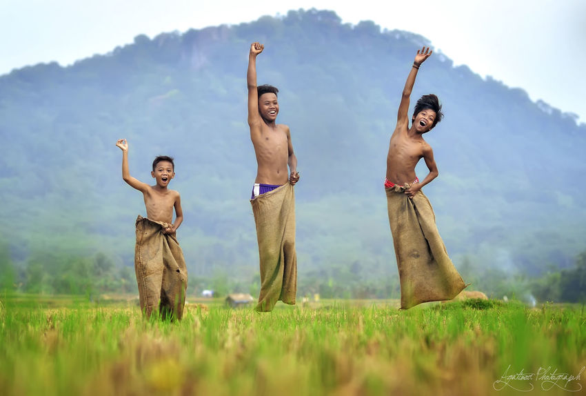 Day Field Front View Full Length Grass Happiness Landscape Leisure Activity Lifestyles Looking At Camera Men Mid Adult Men Mountain Nature Outdoors Portrait Real People Shirtless Sky Smiling Standing Togetherness Two People Young Adult Young Men