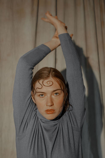Portrait of woman with arms raised against wall
