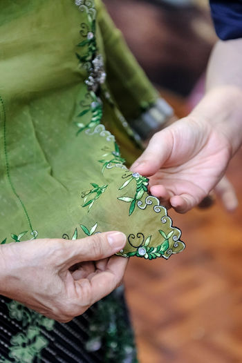 Midsection of women analyzing embroidery on green fabric