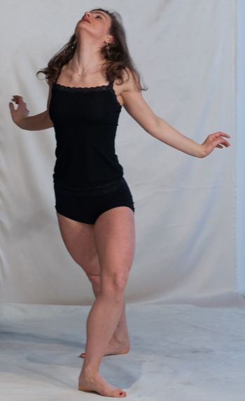 Young woman practicing dance against backdrop