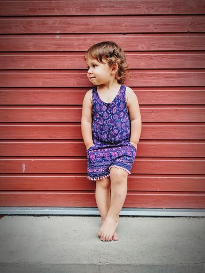 Full length of cute girl looking away while leaning against wall
