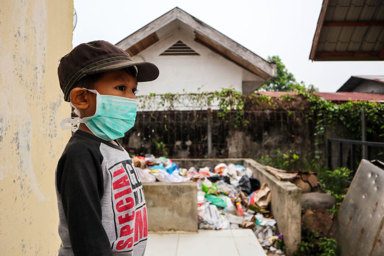 Side view of boy wearing pollution mask while standing on sidewalk