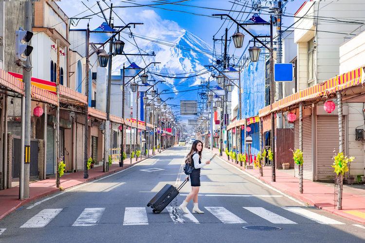 Woman walking on road along buildings