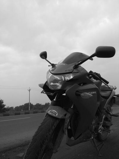 Close-up of person riding motorcycle on road against sky
