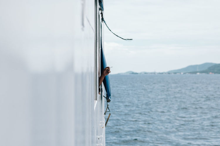 Man smoking by window of nautical vessel on sea against sky