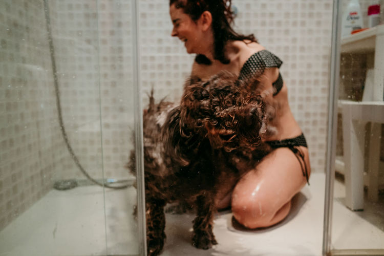 Young woman and dog in bathroom