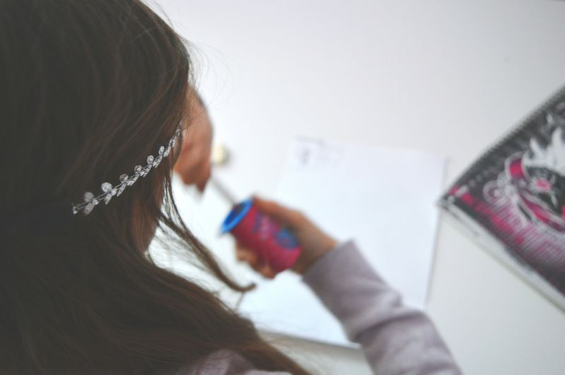 Cropped Image Of Girl Drawing On Table At Home
