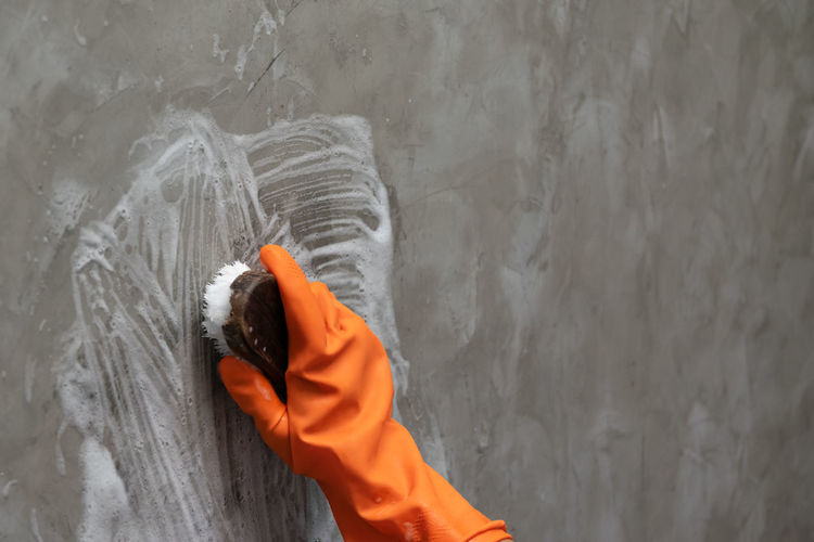 Woman's hand wearing orange rubber gloves is used to convert scrub cleaning on the concrete wall. Human Hand Hand Human Body Part One Person Holding Real People Motion Outdoors Day Orange Color Wall - Building Feature Nature Gray Lifestyles Water Unrecognizable Person Men Human Limb Washing Cleaning Tool House Keeper Homemade Wall Concrete
