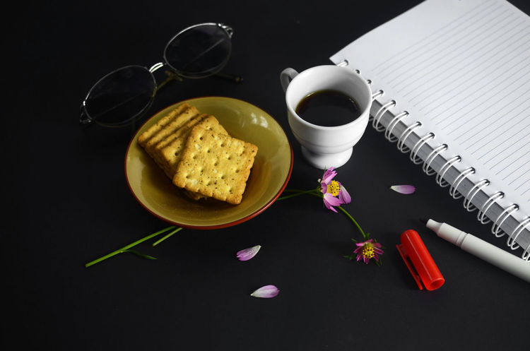 Drink Food And Drink Coffee - Drink Indoors  Studio Shot Black Background Healthy Eating Food Freshness Pen Red Book Paper Petals Table Sketch Pad Diary Flower Biscuits Sunglasses