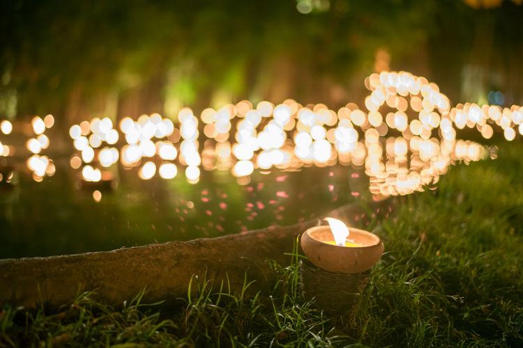 Close-Up Of Illuminated Diya On Field At Night
