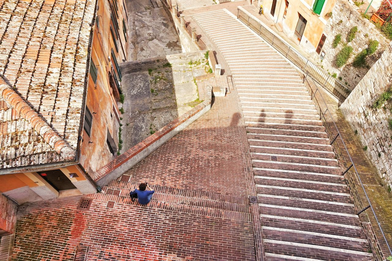High angle view of person sitting on steps