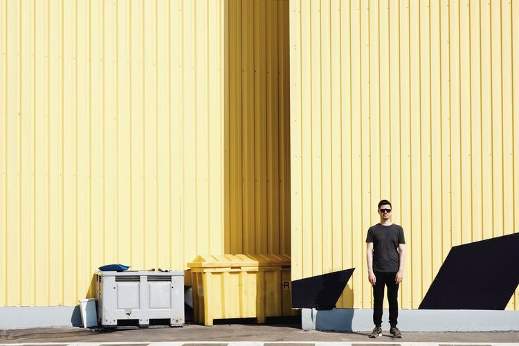 Full Length Of Man Standing Against Yellow Cargo Container