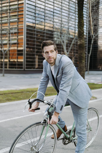 Portrait of young man riding bicycle on city