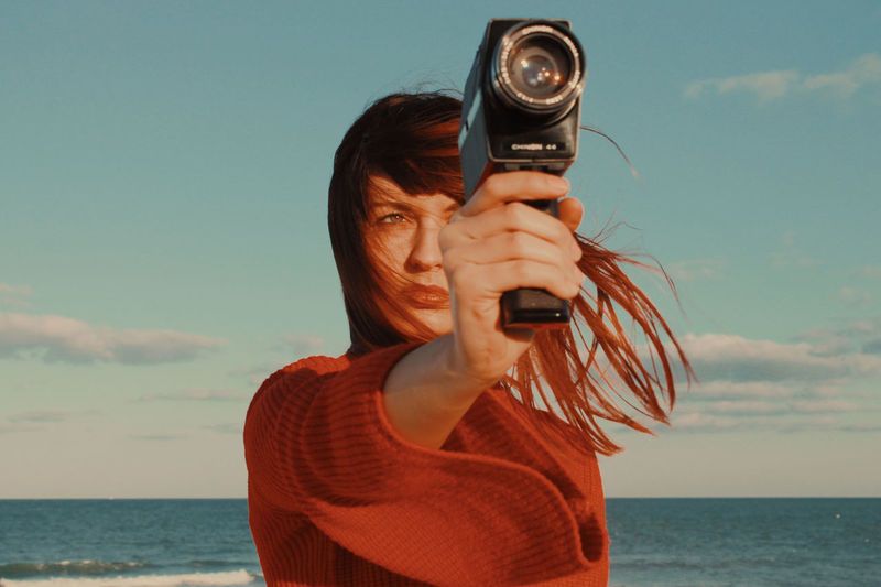 Portrait of woman photographing sea against sky