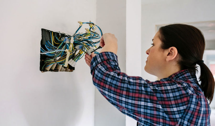 Woman examining cables in house