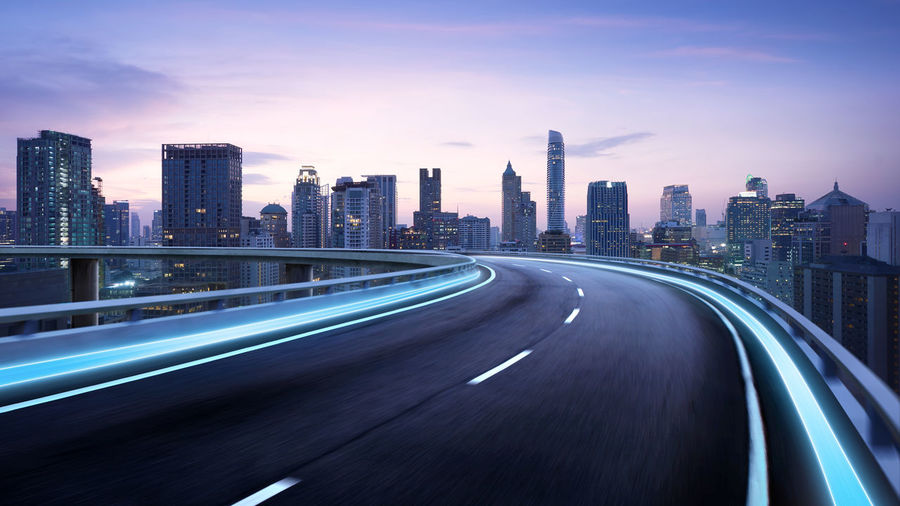 City Architecture Transportation Built Structure Motion Office Building Exterior Skyscraper Speed Building Exterior Road Blurred Motion Urban Skyline Cityscape Highway Street Sky Long Exposure Building Illuminated City Life Modern Multiple Lane Highway No People Outdoors Light Trail Road
