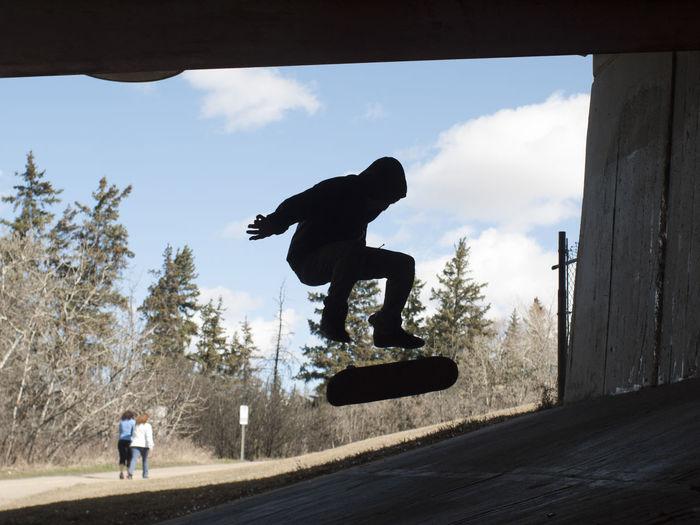 Silhouette man jumping with skateboard below bridge