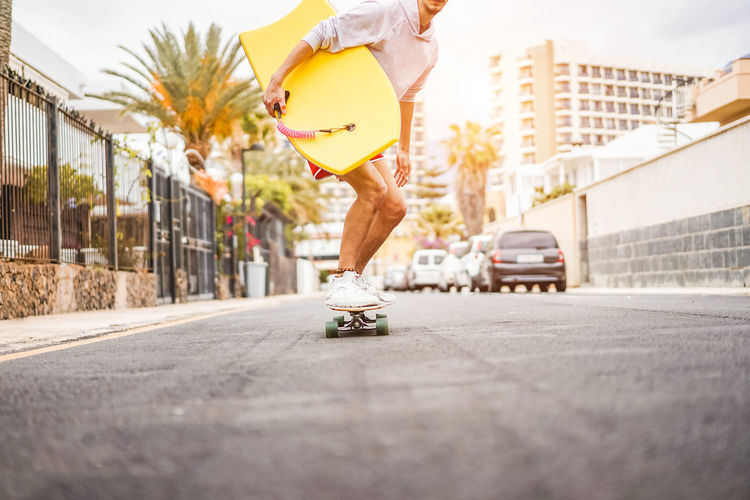 Low section of man skateboarding on street in city