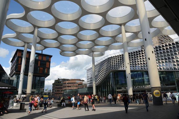 People walking on modern building in city against sky