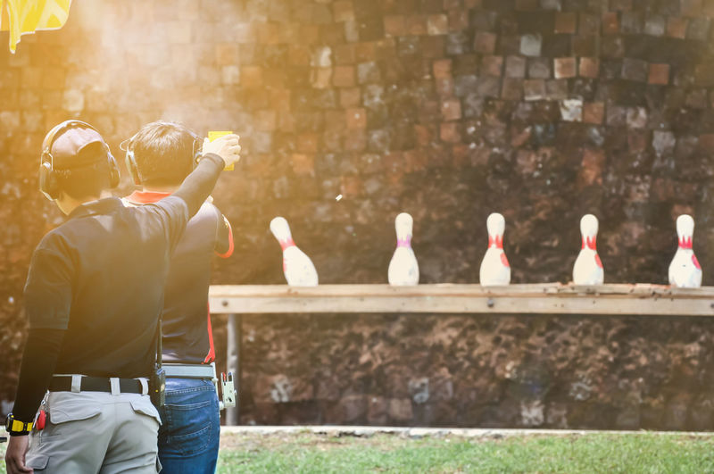 Shooting competition has a goal at the front. Isolated Shiny Shiny Things Ammo Ammunition Bullet Bullets Competition Copper  Day Firearms Guns Handgun Men Outdoors Projectile Real People Rifle Shooting Games Shooting Range  Shot Standing Tool Weapon