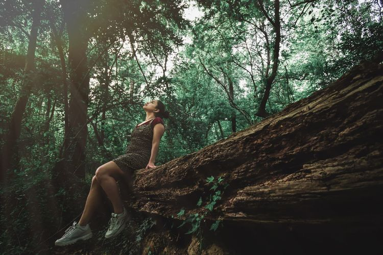 Woman sitting on tree trunk in forest