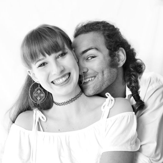 Portrait of happy couple against wall
