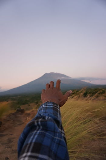 Cropped hand of man gesturing towards mountain against sky during sunset